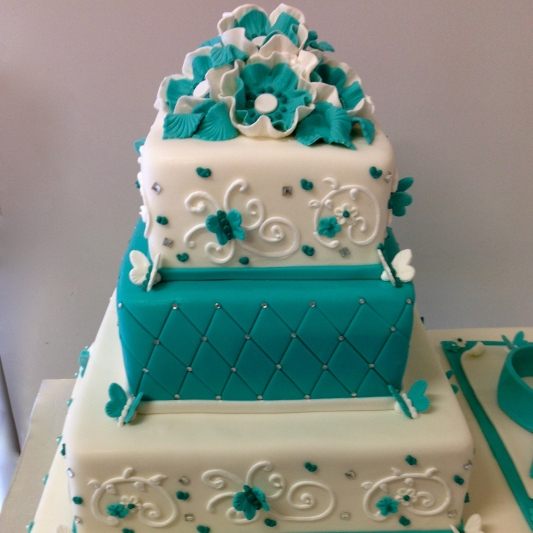An elegant teal and white cake we created for a fundraising event. All decorations were handmade including the iced lacework.