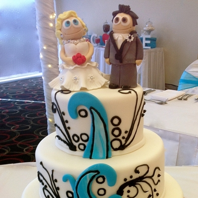 A wedding cake we created to match the decor and bridesmaid colours along with a likenesses of the bride and groom.